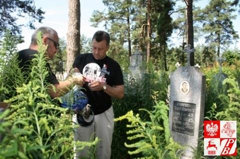 Eugeniusz Gosiewski i Mieczysław Jaśkiewicz zapalają znicz przy grobie żołnierza AK Pawła Jasiewicza
