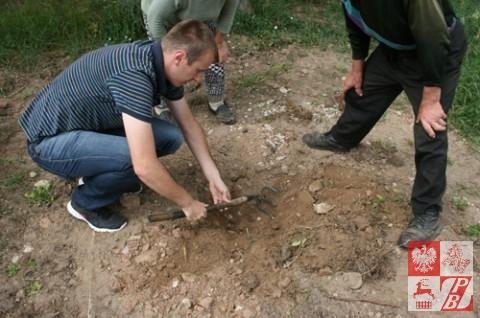 Działacze ZPB pod nasypaną przez wandali ziemią szukają miejsca, w którym tamci spiłowali krzyż