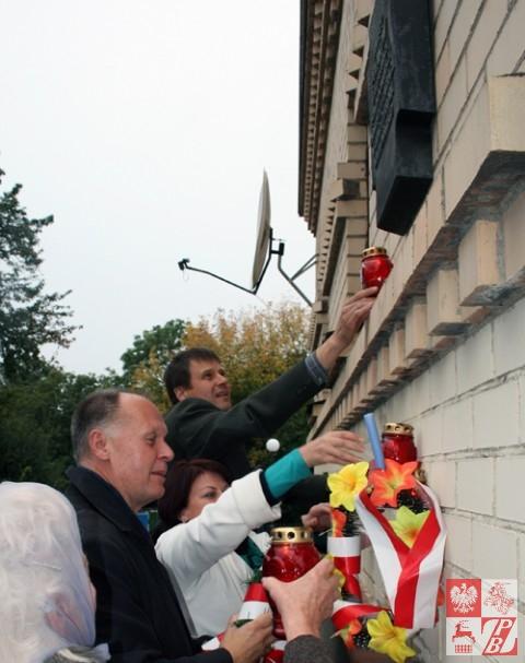 Konsul generalny RP w Grodnie Andrzej Chodkiewicz stawia wraz z działaczami ZPB znicz pod tablicą pamiątkową na Domu Polskim