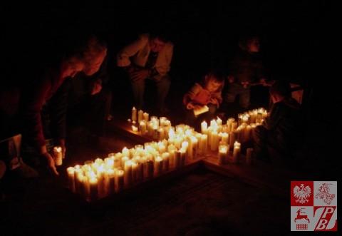 Plonące świece na przyniesionym przez młodzież pod ołtarz z relikwiami drewnianym krzyżu