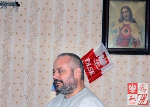 Eugeniusz Gosiewski na tle flagi polskiej, wiszącej na ścianie w mieszkaniu Edmunda Lebiedzia