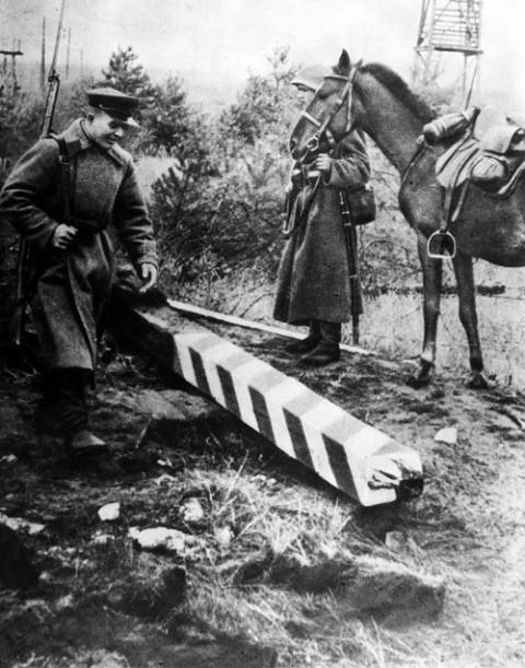 Żołnierz sowiecki niszczy polski słup graniczny, październik 1939 r.