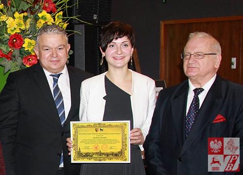 """Podziękowanie od społeczności Wołowa dla zespołu """"Jednym Głosem"""" trzyma Olga Guczek"""