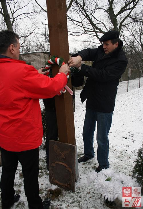 Mieczysław Jaśkiewicz i Józef Porzecki przywiązują wieniec do krzyża w Kulbakach