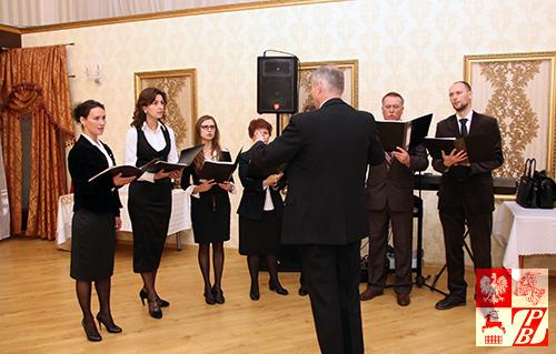 """Śpiewając kolędy, w świąteczny nastrój wprowadza obecnych na przyjęciu grupa wokalna chóru reprezentacyjnego ZPB """"Głos znad Niemna"""""""