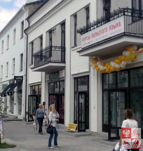 Przechodnie zauważają ogłoszenie o naborze na naukę języka polskiego