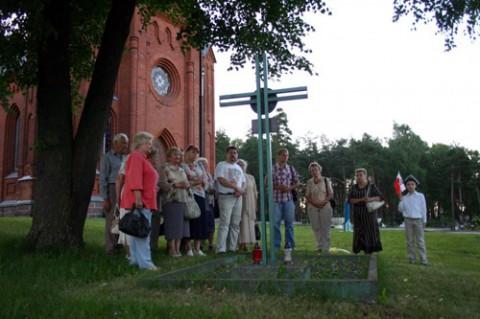 """Przy Czerwonym Kościele, obok pomnika-krzyża """"Straż Mogił Polskich"""", ustanowionego niedaleko świątyni. Krzyż wzniesiono na cześć żołnierzy Armii Krajowej oraz jako pomnik dla cywilnej ludności miasteczka, wymordowanej w latach 1939-1945"""