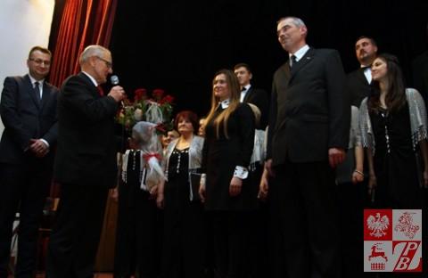 Jan Chojnowski w imieniu organizatorów wręcza kwiaty derygence chóru Weronice Szarejko