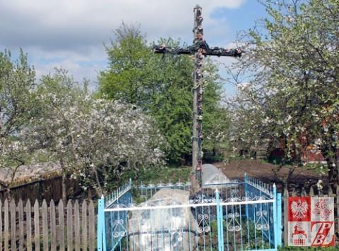Stary, spróchniały krzyż przydrożny przy pomniku